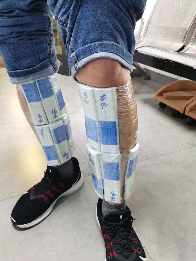 Foto van twee benen waarop allerlei smokkel-hardware getapet zit.