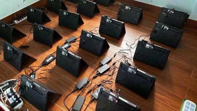 Foto van een vloer gevuld met opstaande, identieke game-laptops om cryptovaluta mee te delven.